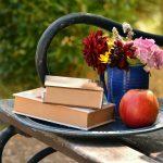 Bücher und Blumen auf der Bank
